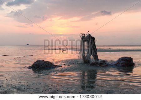 Asian fisherman prepares fishing nets for night fishing at sunset.