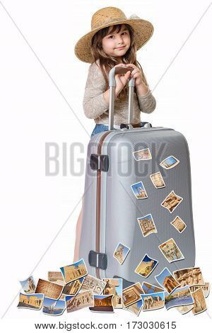 Long haired little girl with straw hat is standing and leaning on a suitcase. Photos of the sights of Egypt flies around the suitcase. All is on the white background. Vertically.