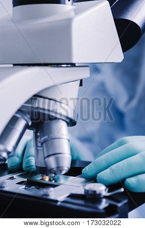 Close up view of scientist hands with gloves set the sample in the microscope for research