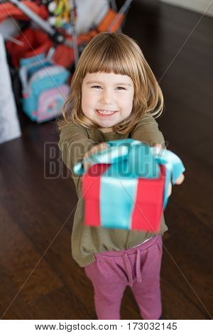 portrait of three years old caucasian blonde child indoors with green shirt offering or giving red and blue gift box in hands with funny expression face