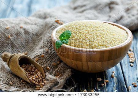 Couscous In A Wooden Bowl And Scoop With Wheat.