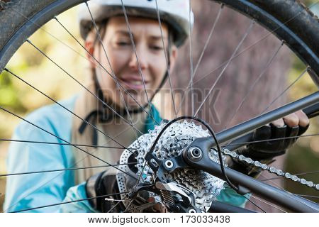 Female mountain biker examining wheel of her bicycle in the forest