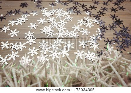 Small candles and snowflake scattered on wooden table during christmas time