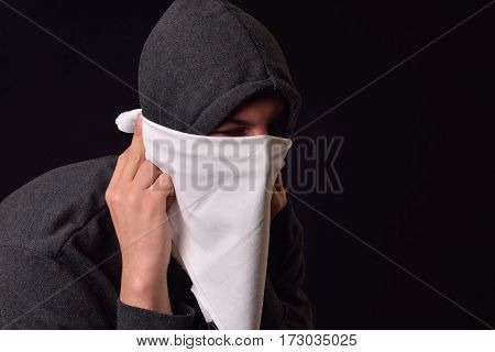 Close Up Of A Young Man Puts On His Face A White Scarf Not Be Recognized And Wearing Black Hoodie Re