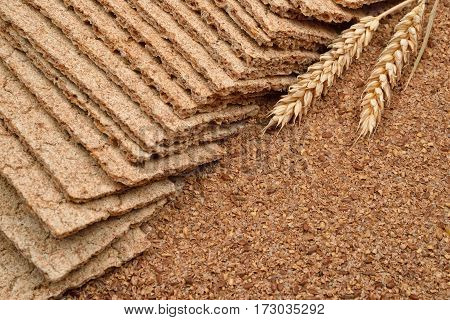 Dry diet crisp breads integral wheat flour with fresh ears wheat on wooden background. From raw material to the finished products. Healthy organic food