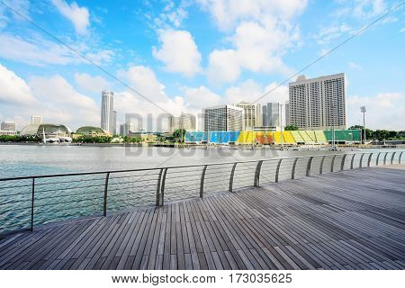 cityscape and skyline of modern city from wood footpath near river in blue cloud sky