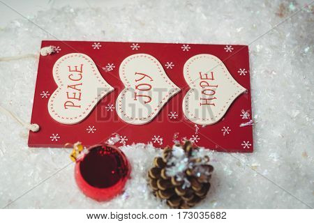 Christmas label with massages and christmas ornaments on snow during Christmas time