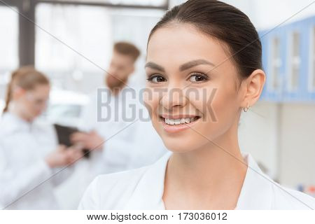 Close-up portrait of young woman in white coat smiling at camera in lab
