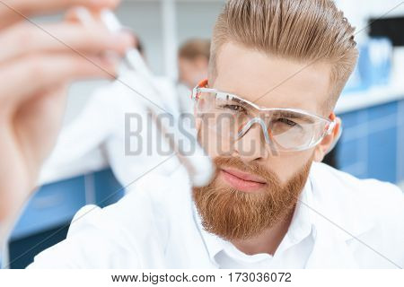 Close-up view of bearded chemist in protective goggles inspecting test tube in lab