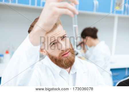 Young bearded chemist in white coat examining test tube in laboratory