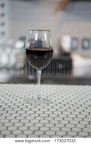 Glass of red wine on counter in bar