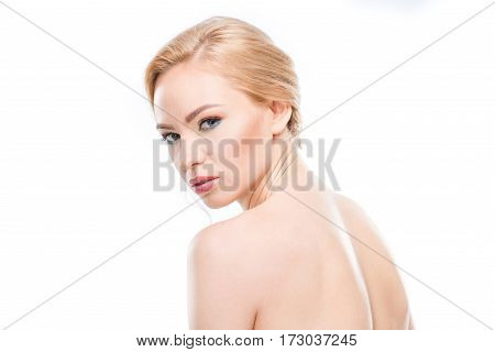 Gorgeous naked blonde woman looking at camera on white body care concept