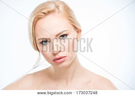 Beautiful young serious woman with stylish makeup looking at camera skincare concept