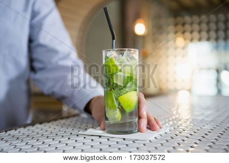 Close-up of man holding glass of gin in bar