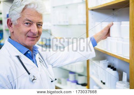 Portrait of pharmacist in lab coat checking medicines in pharmacy