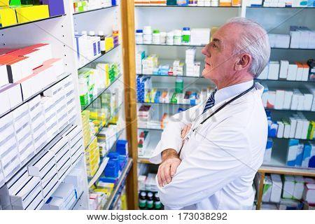 Pharmacist in lab coat checking medicines in pharmacy