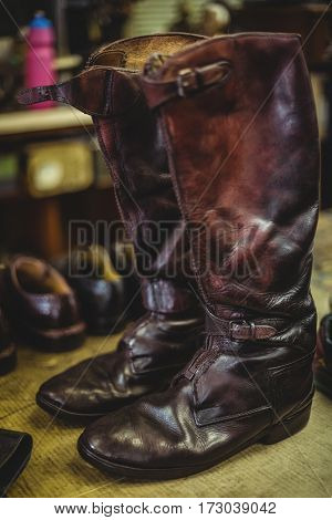 Pair of long leather boots in workshop