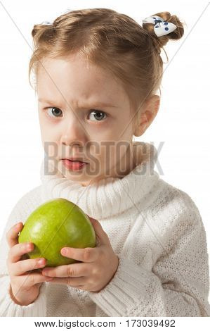 Unhappy three-year girl holding green apple, on white background