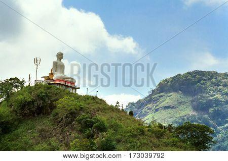 Scenic view with tropical forest, mountains, and Buddha sculpture in Sri Lanka