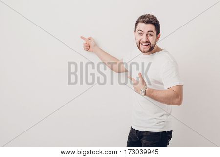 handsome smilling man with beard pointing copy space. young man in t-shirt looking at camera and pointing away against white wall. soft light