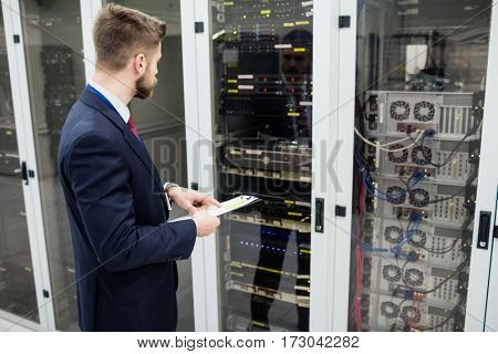 Technician holding clipboard while analyzing server in server room