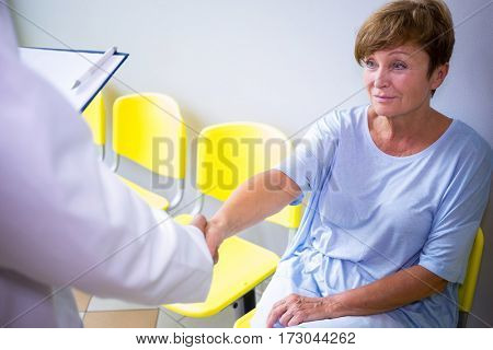 Doctor shaking hand with patient in waiting room of a hospital