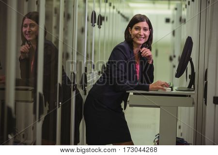 Portrait of technician working on personal computer while analyzing server