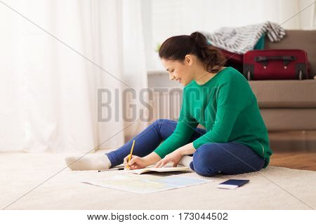 vacation, tourism, travel and people concept - happy young woman with notebook, passport and map at home going on trip