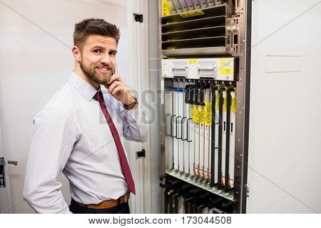 Portrait of technician talking on mobile phone while working in server room