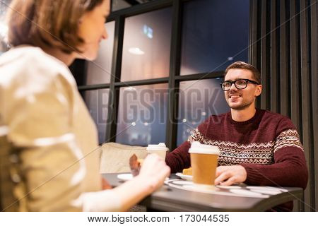 food, people and dating concept - happy couple with coffee in paper cups eating cake or pie for dessert at cafe