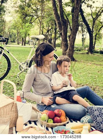 Mom and son picnic in a park.