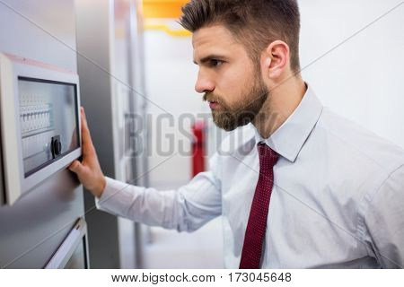 Technician looking at server cabinet in server room