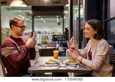 technology, eating, vegetarian food and people concept - happy couple or friends with smartphones having dinner at vegan restaurant