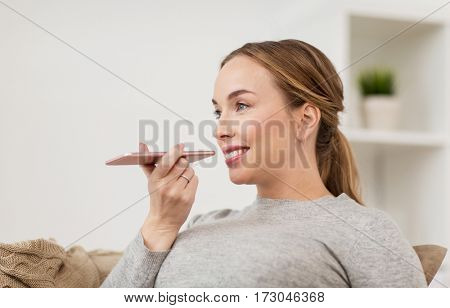 people, technology, communication and leisure concept - happy young woman using voice command recorder or calling on smartphone at home