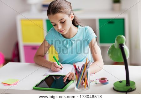 people, children, education and learning concept - girl with tablet pc computer writing to notebook at home