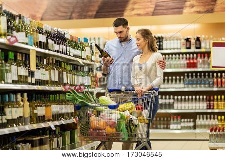sale, consumerism, alcohol and people concept - happy couple with bottle of white wine and food in shopping cart at liquor store or supermarket