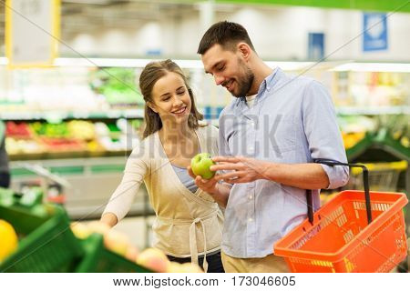 shopping, food, sale, consumerism and people concept - happy couple buying apples at grocery store or supermarket
