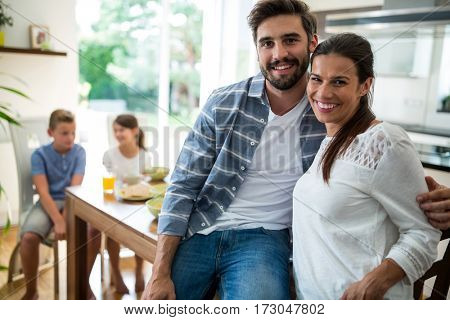 Portrait of couple sitting with arm around on dining table at home