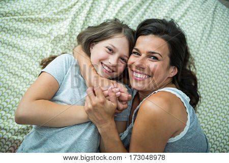 Portrait of mother and daughter playing on bed at home
