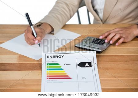Businesswoman using calculator to calculate finance in office