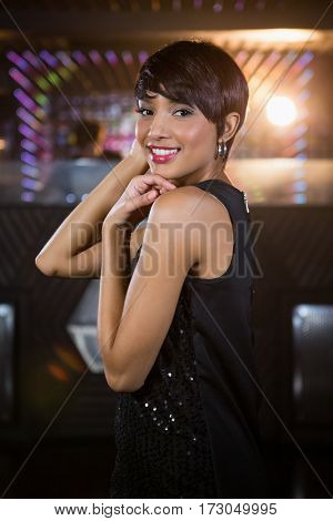 Portrait of young woman dancing on dance floor in bar