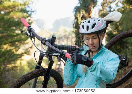 Female mountain biker carrying her bicycle in the forest on a sunny day