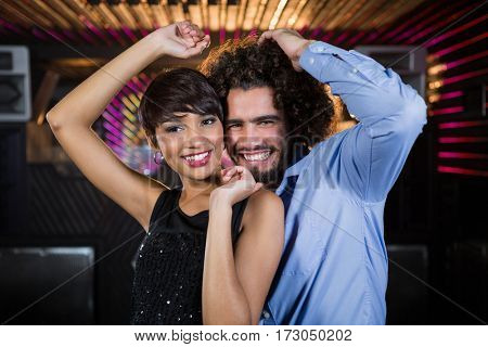 Portrait of cute couple dancing together on dance floor in bar
