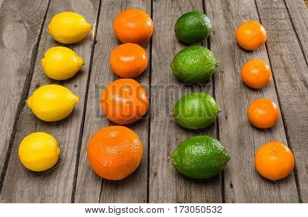 Close-up view of fresh healthy citrus fruits in rows on wooden table