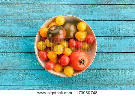 top view of tomatoes in bowl on wooden table