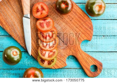 top view of fresh tomatoes on cutting board with knife