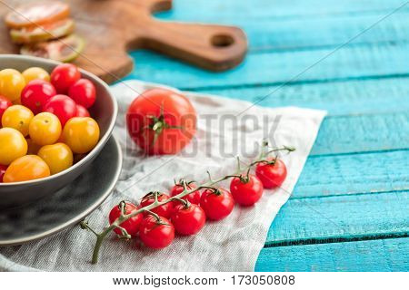 various fresh tomatoes in bowl and cutting board