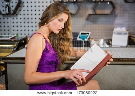 Beautiful woman reading the menu in bar