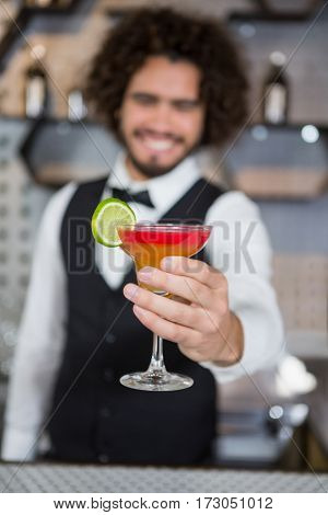 Smiling bartender holding glass of cocktail in bar counter at bar