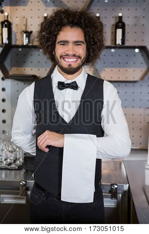 Portrait of smiling waiter ready for serving customers in bar